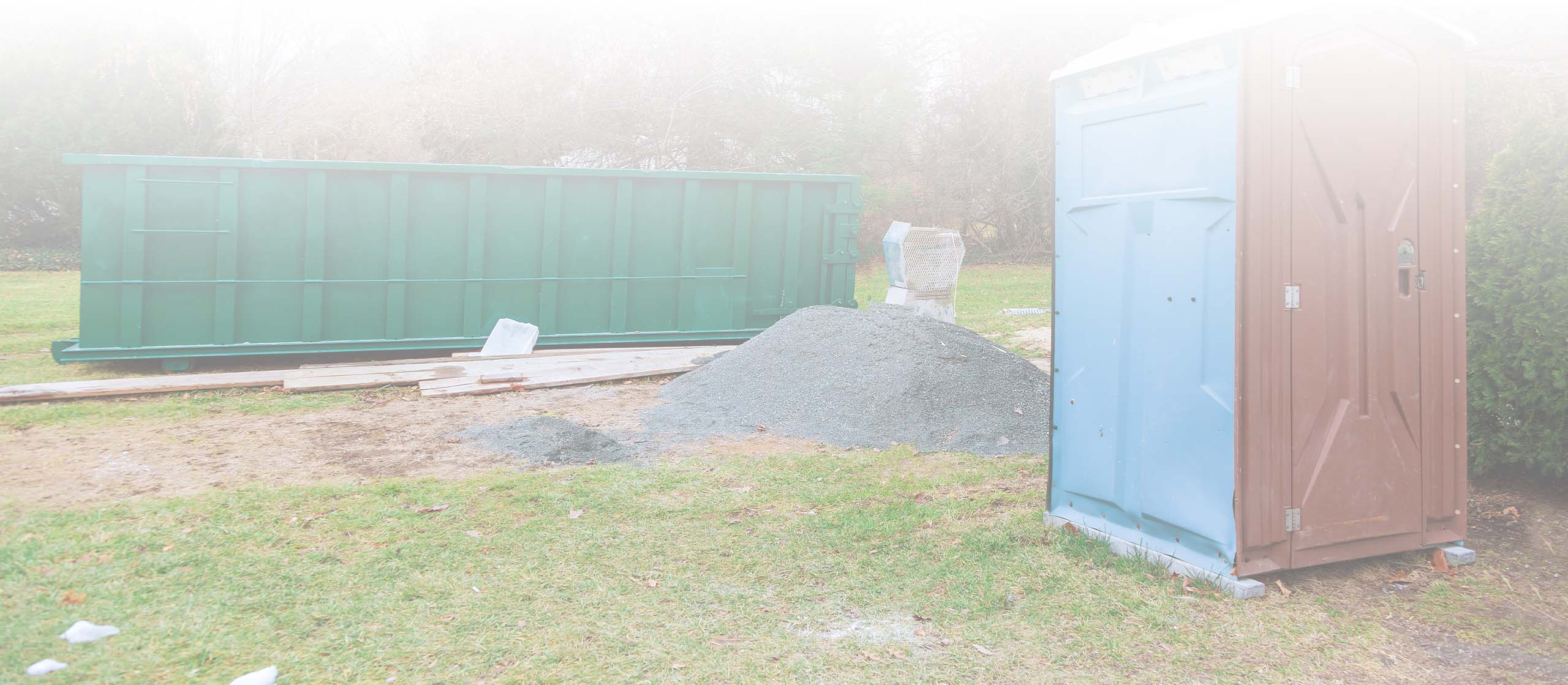Outdoor work site with green dumpster and portable toilet on ab8waste.com